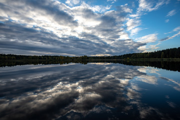 Fototapeta calm lake in bright sun light with reflections of clouds and trees and blue sky