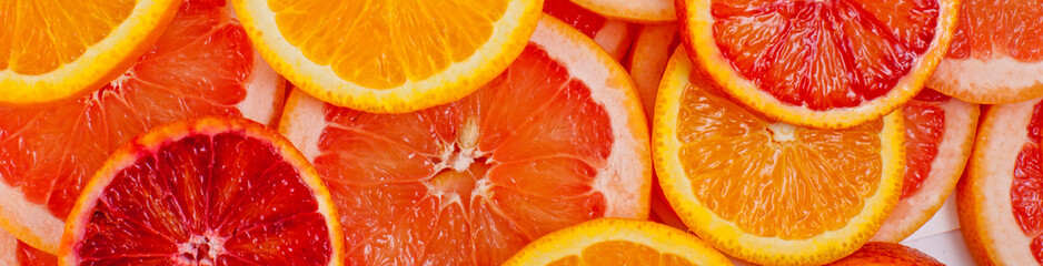 Different kinds of oranges and grapefruit slices background