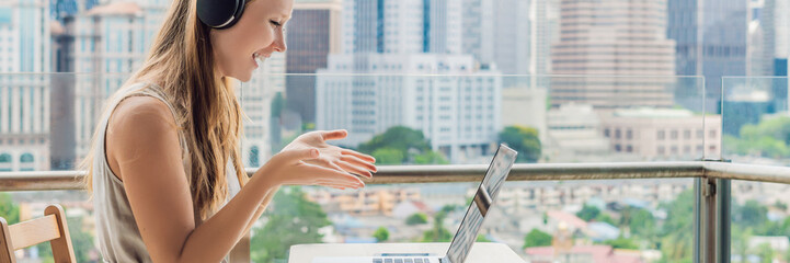 Young woman teaches a foreign language or learns a foreign language on the Internet on her balcony against the backdrop of a big city. Online language school lifestyle BANNER, LONG FORMAT
