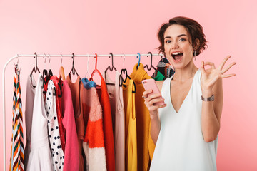 Happy woman stylist posing isolated over pink wall background near a lot of clothes using mobile phone.