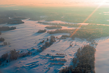 Aerial view winter sunrise over snow-covered space of the forest territory. Aircraft photography from above.