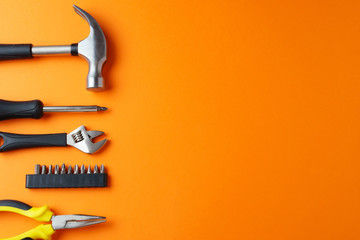 Hammer, pliers, screwdriver on an orange background, top view, a place for an inscription