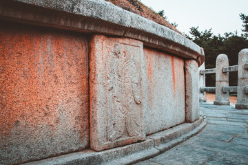 Relief carvings of Oriental zodiac god, half man, half animal, standing guard around the tomb of General Kim Yusin in Gyeongju, South Korea. Known as the Hero of the Silla Kingdom