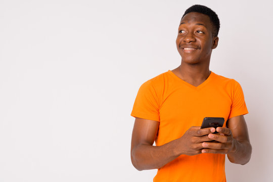 Portrait of young happy African man thinking while using phone