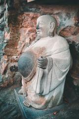 Laughing buddha stone statue in Yonggungsa Buddhist temple in Busan, South Korea