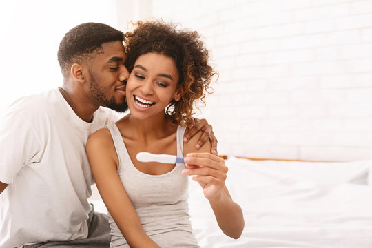 Happy couple holding positive pregnancy test on bed