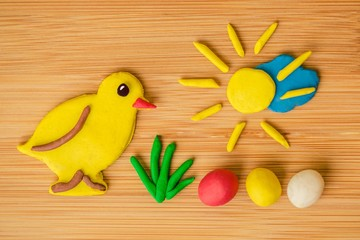 Funny spring Easter image made of plasticine, a yellow chicken, green grass, colorful eggs - red, yellow and white, golden sun shining over blue cloud on wooden background, warm colors