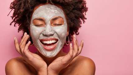 Cheerful young woman has Afro hairstyle, touches cheeks, has clay mask on face, enjoys softness, has beauty treatments at home, poses half naked, isolated over pink background. Skin care concept