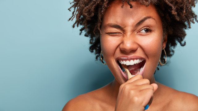 Close up shot of happy joyful funny dark skinned young woman has Afro hair brushes teeth actively with toothbrush, opens mouth broadly, blinks eye, shows bare shoulders, cares of oral hygiene