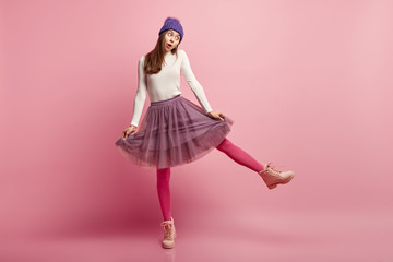 Isolated shot of surprised European woman in fashionable clothes, dances, keeps hands on skirt, has eyes popped out, isolated over pink background. Full length view. People, fashion concept.