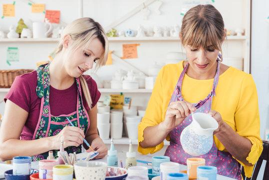 Two women painting own ceramic tableware in DIY workshop