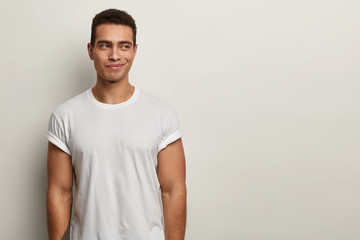 Photo of satisfied smiling man with thoughtful expression, muscular body, wears white t shirt in one tone with background, thinks about how spend next weekend, has tattooed arm. Youth concept