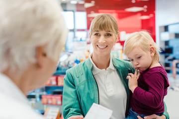 Mother with daughter in pharmacy at the counter