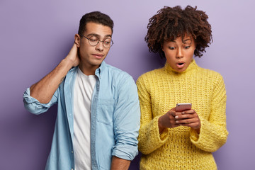 Shocked woman reads recieved notification, stares at cell phone, curious guy in round spectacles peeks at screen, wants to read message. Diverse couple with modern technolgy against purple wall