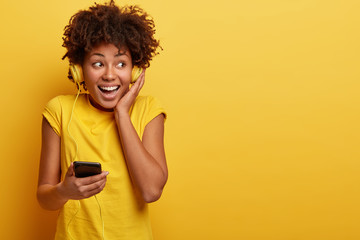 Indoor shot of attractive young woman listens cool song with headphones and mobile phone, has nice quality of sound, focused away, has broad smile, good mood, dressed in casual yellow attire