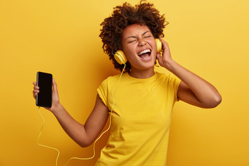 Photo of amused beautiful dark skinned lady enjoys listening favourite music in headphones, feels carefree, satisfied with quality of sound, likes her playlist, laughs out from positive emotions
