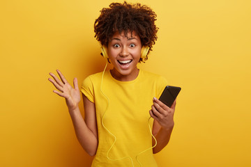 Photo of laughing impressed lovely woman looks happily at camera, raises palm, holds cell phone, ready to go for walk with music, likes yellow colour, looks directly at camera with satisfaction