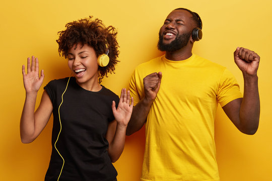 Photo of joyful positive ethnic female and male teenagers sing from pleasure, gesture actively, listen music from playlist, enjoy perfect sound, stand next to each other, isolated over yellow wall