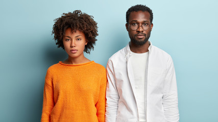 Indoor shot of serious ethnic female and male partners think on future collaboration, stand closely to each other, look directly at camera. Dark skinned groupmates meet for preparing common task