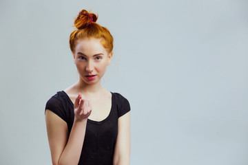 Portrait of a nice woman showing come to me gesture. Female model with red hair tied in knot, wearing black shirt on gray background with copy empty space