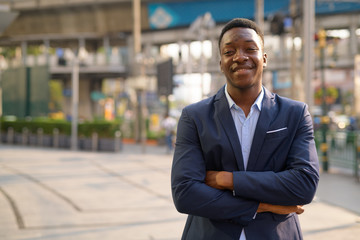 Young happy African businessman smiling with arms crossed in the city