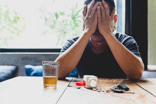 Depression man hand on his face with glass of alcohol and pills on the table.