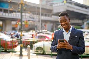 Young happy African businessman using phone in the city