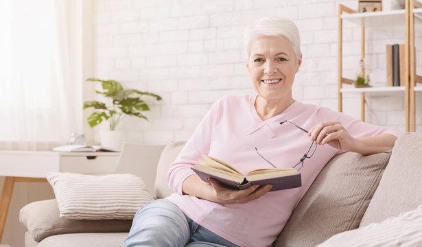 Smiling senior woman reading book at home