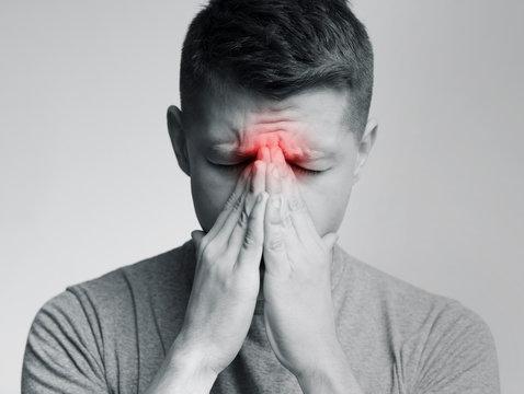 Sad man holding his nose because sinus pain