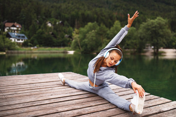 Young sports woman stretching legs at dock on the lake in the mountains