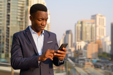 Young handsome African businessman using phone against view of the city
