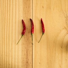 3 dried red raw hot chili cayenne pepper on a wooden plate. Spicy food. Top view, flat