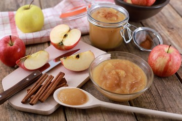 homemade apple jam, with fresh apples and spices with wooden spoon on wooden rustic table