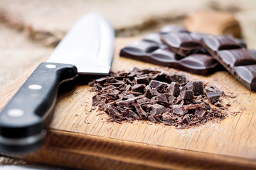 Chopped dark chocolate on wooden cutting board