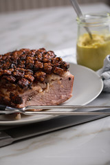 Deutscher Krustenbraten aus Schweinefleisch mit Senf auf Teller mit Küchenmesser und Fleischgabel auf Marmor Hintergrund