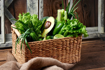 Green vegetables and fruits and greens in a brown wicker basket on a wooden background. Healthy eating concept