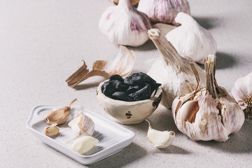 Variety of fresh organic garlic bulbs whole and peeled and cloves of black fermented garlic with ceramic grater over grey spotted background. Close up