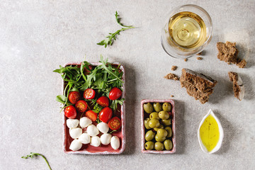 Mozzarella, cherry tomatoes, olives antipasto appetizers served in pink ceramic rectangular plates with olive oil, glass of white wine, arugula, rye bread over grey texture background. Flat lay, space