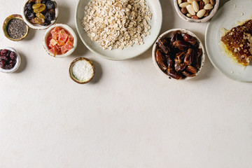 Variety of dried fruits, nuts, honey and oat flakes in ceramic bowls for cooking homemade healthy breakfast muesli or granola energy bars over white texture background. Flat lay, space.