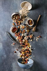 Variety of dried fruits, nuts, honey and oat flakes pours in ceramic bowl for cooking homemade healthy breakfast muesli or granola energy bars over blue texture background. Flat lay, space.