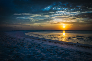 Sunset in the Maldives with reflection of the Sun in the water and blue and orange colored clouds in the sky