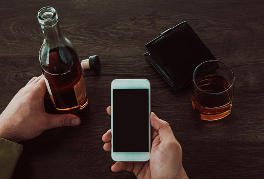 A man holds a mobile phone in his hands. Next on the table is a glass and a bottle of whiskey.