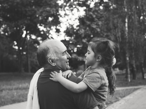 Black and white portrait of Happy grandfather and grandaughter playing at the park