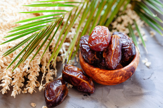 Bowl of raw organic medjool dates with leaves and flowers of date palm