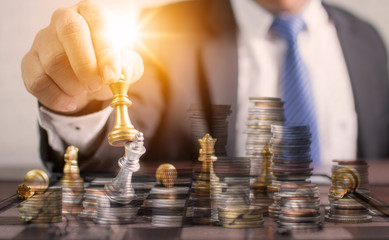 Successful planning and strategic concept, business man holding chess and move forward for win and victory with staked money coins