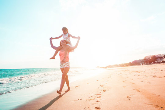 Mother and daughter having fun on tropical beach