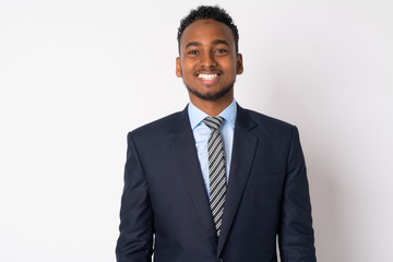 Portrait of happy young African businessman in suit smiling