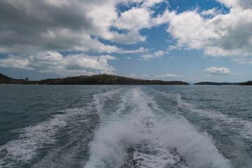 Blick vom Heck eines Motorboot in die aufgewühlte Fahrrinne unter wolkigem Himmel