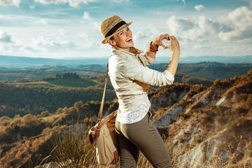 woman on summer hiking in Tuscany showing heart shaped hands