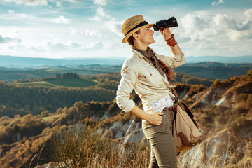 smiling woman looking into distance through binoculars